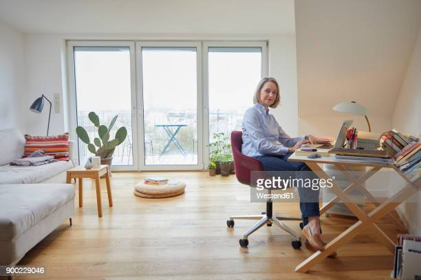 Mature woman at home using laptop at desk