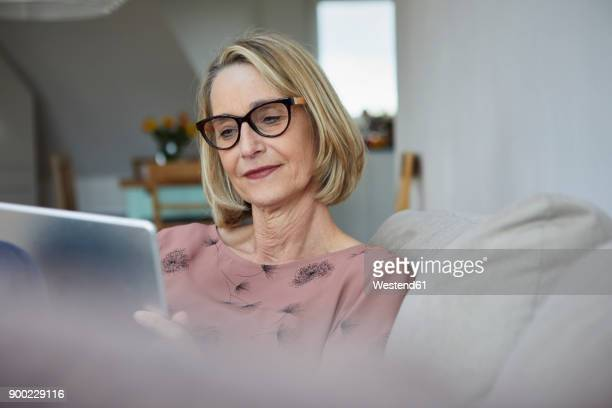 mature woman at home using tablet on the sofa - equipment stock pictures, royalty-free photos & images