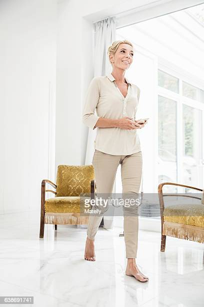 Mature woman at home, walking across room