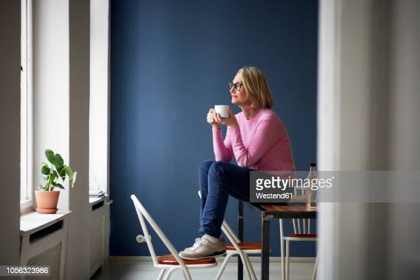 mature woman at home with cup of coffee looking out of window - beschaulichkeit stock-fotos und bilder