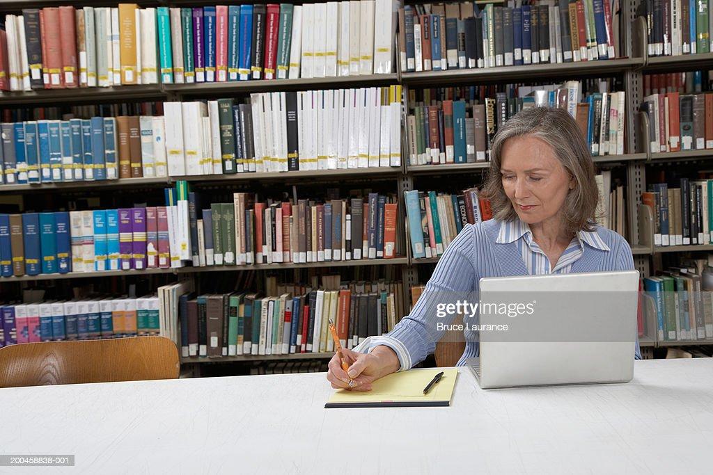 Mature woman at library table, using laptop and writing notes : Bildbanksbilder