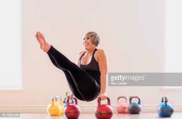 Mature woman balancing between two kettlebells