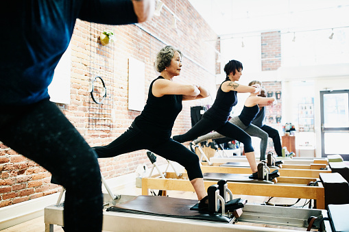 Mature woman balancing on reformer while doing roman splits during class in pilates studio - gettyimageskorea