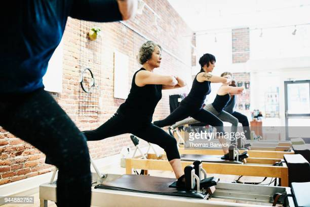 Mature woman balancing on reformer while doing roman splits during class in pilates studio