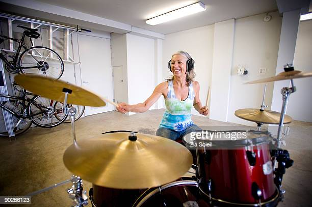 mature woman bangs drums in garage - drum kit stock pictures, royalty-free photos & images