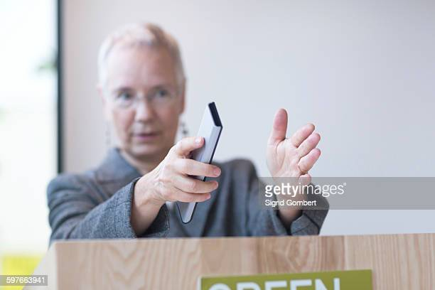 mature woman behind podium giving lecture holding remote control, gesticulating - sigrid gombert stock pictures, royalty-free photos & images