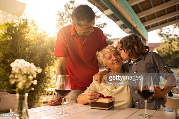 Mature woman being kissed by her grandson oh her birthday.