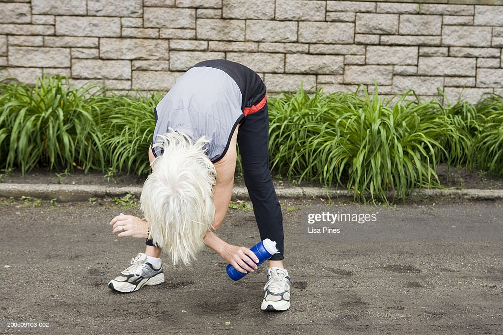 Mature Woman Bending Over Outdoors Stock Photo - Getty Images-4964