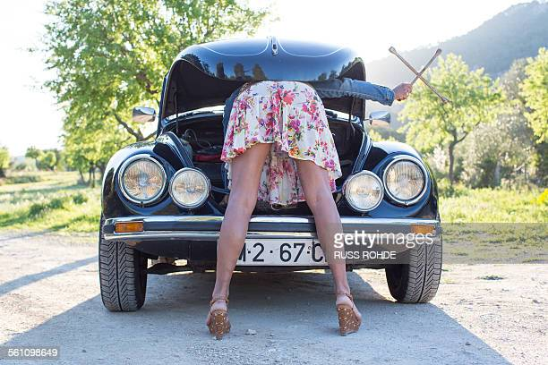 mature woman bent over car, looking in bonnet - older woman bending over stock pictures, royalty-free photos & images