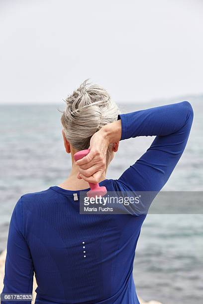 Mature woman beside sea, exercising with hand weights, rear view