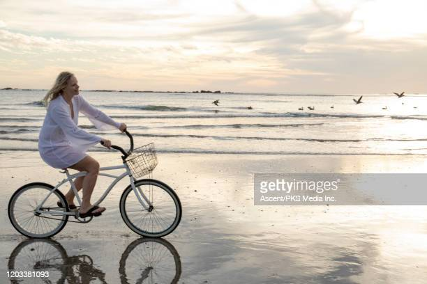mature woman bikes along tidal flat at sunrise - flowing cape stock pictures, royalty-free photos & images