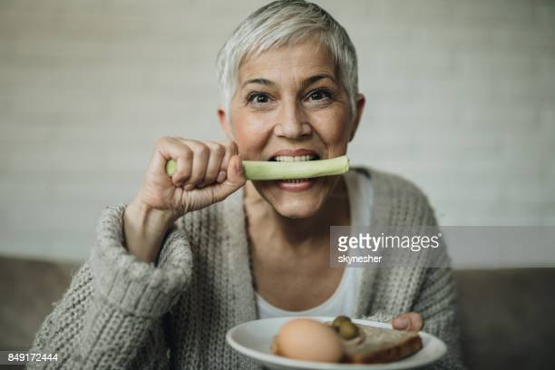 Mature woman biting celery and looking at camera.
