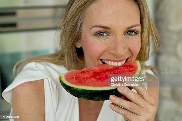 Mature woman biting watermelon