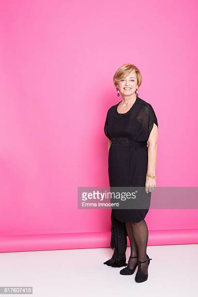 mature woman, black dress, pink background - black dress stock pictures, royalty-free photos & images