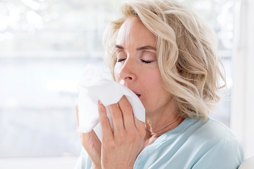 Mature woman blowing nose on tissue - gettyimageskorea