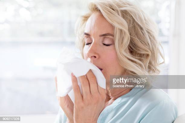 mature woman blowing nose on tissue - cold and flu stock photos and pictures