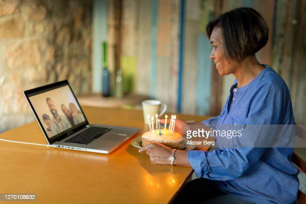 mature woman blowing out birthday cake candles on a video call - évitement photos et images de collection