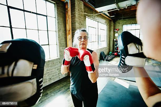 mature woman boxing with coach in gym - boxen sport stock-fotos und bilder