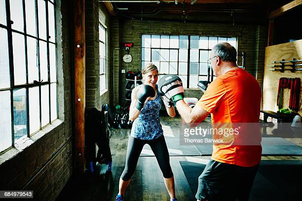 Mature woman boxing with workout partner in gym