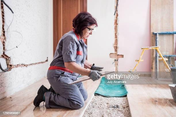 家の部屋の改造でタイルと床を成熟した女性のレンガ造り - ワーキングシニア ストックフォトと画像