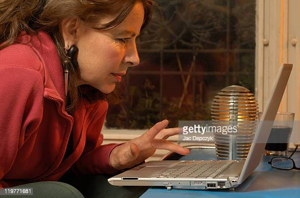 mature woman browsing internet on laptop. - depczyk stock pictures, royalty-free photos & images