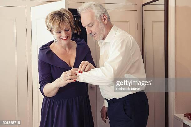 Mature woman buttoning senior man's shirt