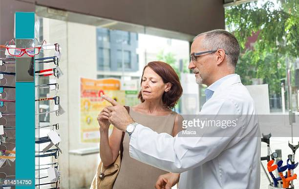 Mature woman buying glasses at the optic or pharmacy