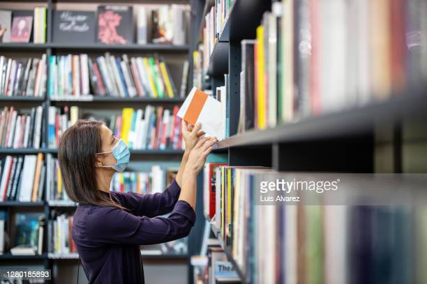 mature woman buying new books at bookshop - choosing stock pictures, royalty-free photos & images