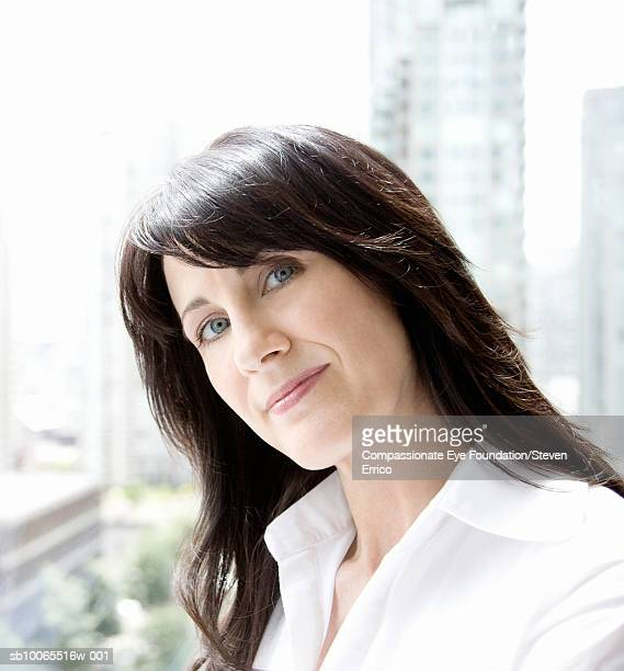 Mature woman by window, portrait, close-up