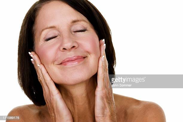 mature woman caressing her face - medelålders kvinnor naken bildbanksfoton och bilder