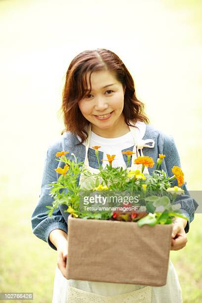 Mature woman carrying flowers in her back yard