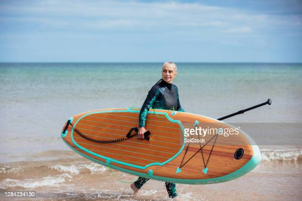 mature woman carrying paddleboard out of the sea - active lifestyle stock pictures, royalty-free photos & images
