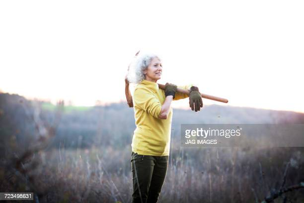 Mature woman carrying pick axe over her shoulder in landscape