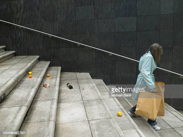 Mature woman carrying shopping bags down steps in rain, side view