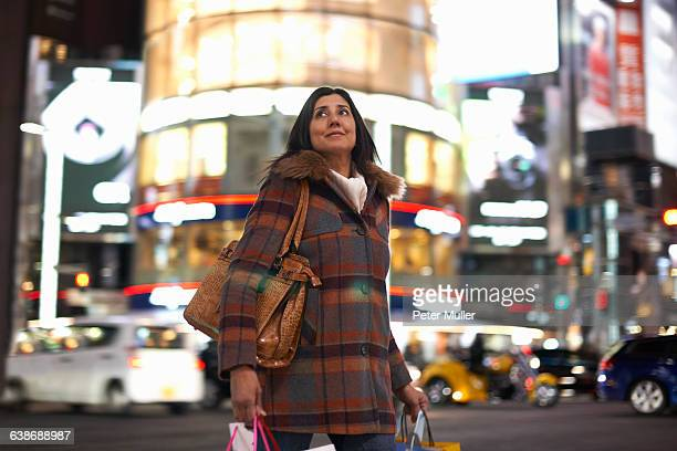 Mature woman carrying shopping bags in city at night looking up, Ginza, Tokyo, Japan