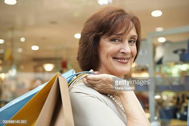 mature woman carrying shopping bags over shoulder, smiling, portrait - alleen één oudere vrouw stockfoto's en -beelden