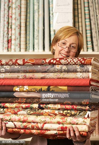 Mature woman carrying stack of rolled textiles, portrait