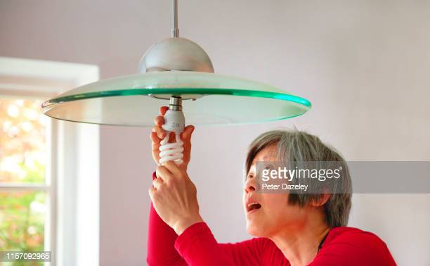 mature woman changing energy efficient lightbulb in her home - energy efficient lightbulb stock pictures, royalty-free photos & images