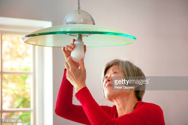 mature woman changing energy efficient lightbulb in her home - mature adult stock pictures, royalty-free photos & images
