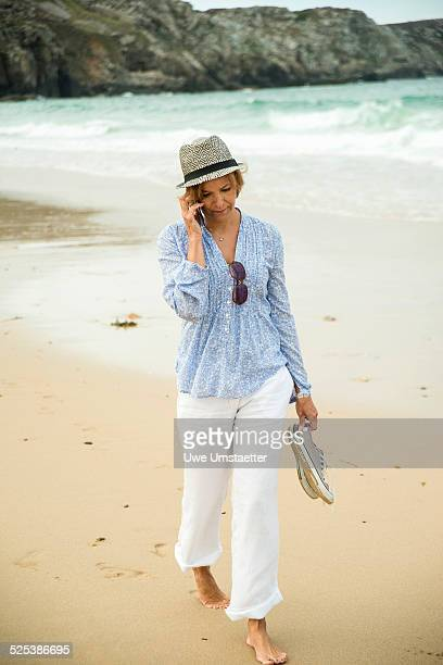Mature woman chatting on smartphone whilst strolling on beach, Camaret-sur-mer, Brittany, France