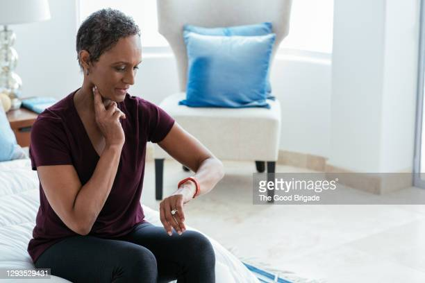 mature woman checking pulse in bedroom - wearable computer stock pictures, royalty-free photos & images