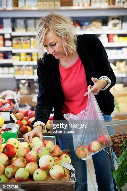 Mature woman choosing apples