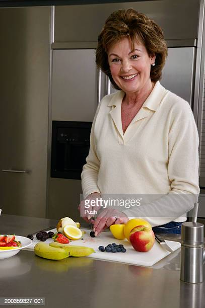 mature woman chopping fruit in kitchen, smiling, portrait - tropische frucht stock-fotos und bilder