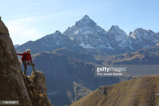 mature woman climber stands on pinnacle above valley and looks towards mountain peak - pinnacle peak stock-fotos und bilder
