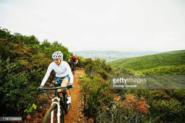 Mature woman climbing hill while riding mountain bike on trail with husband