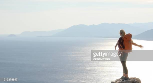 donna matura sale in cima all'apice sopra il mare - vivere semplicemente foto e immagini stock