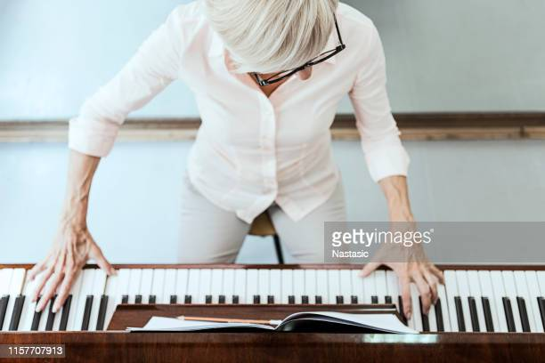 mature woman composer playing piano - piano stock pictures, royalty-free photos & images