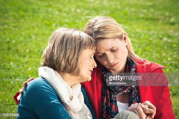 mature woman consoling her mother - depressed mother stock pictures, royalty-free photos & images