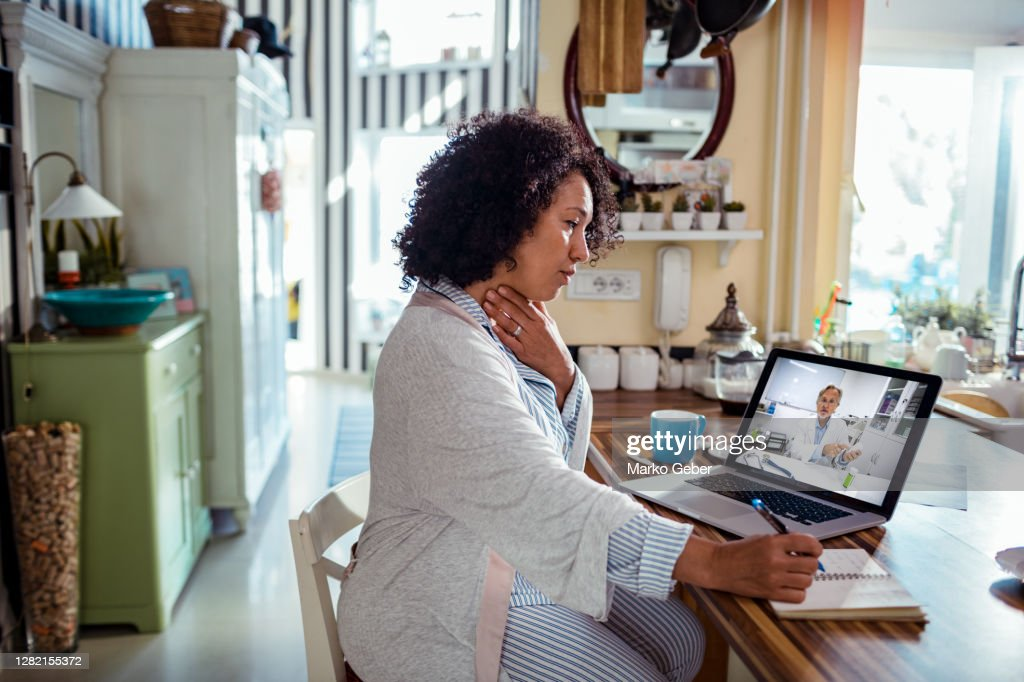 Mature woman consulting with her doctor online : Stock Photo