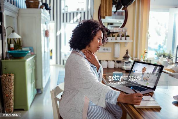 mature woman consulting with her doctor online - healthcare stock pictures, royalty-free photos & images